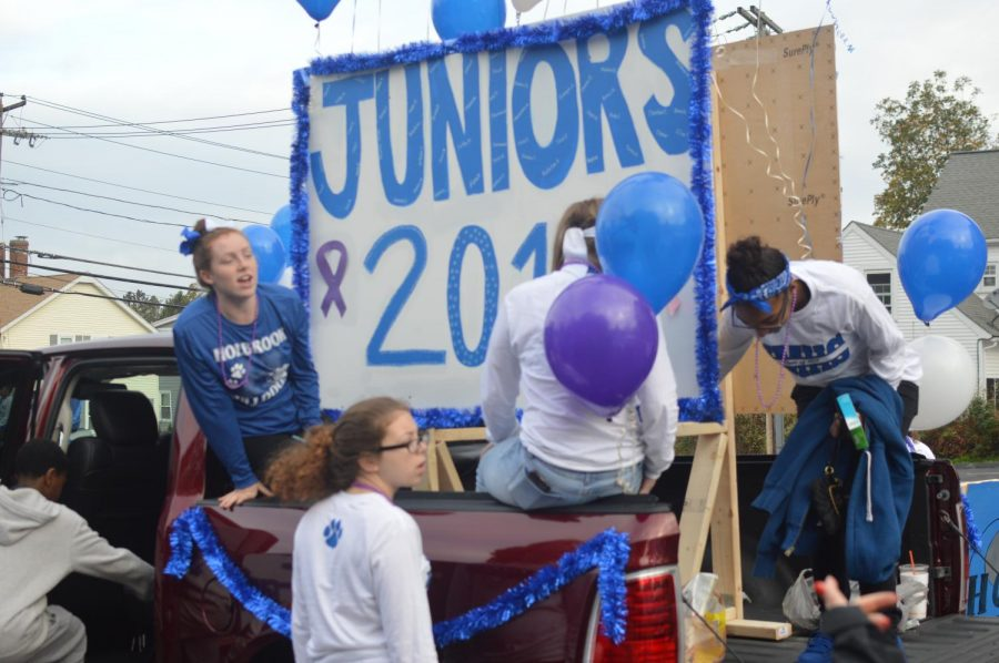 Junior students Katelin Andrews and Hayli Manning work with fellow classmates to tie together their float