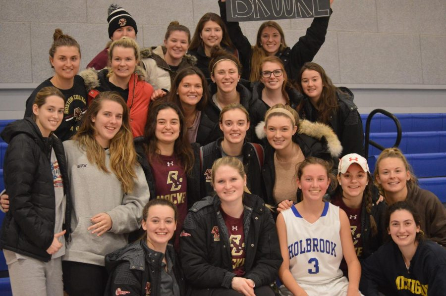 Brooke DiBona with her mentor and the rest of the BC women's hockey team after the Bulldogs JV basketball game.