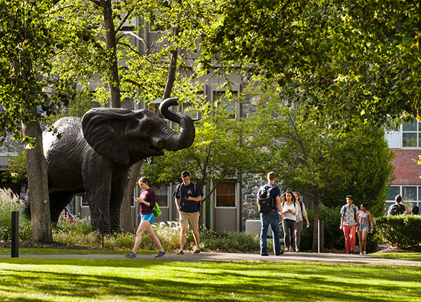 Students of Tufts University are spotted walking to class near the notable 'Jumbo' statue.