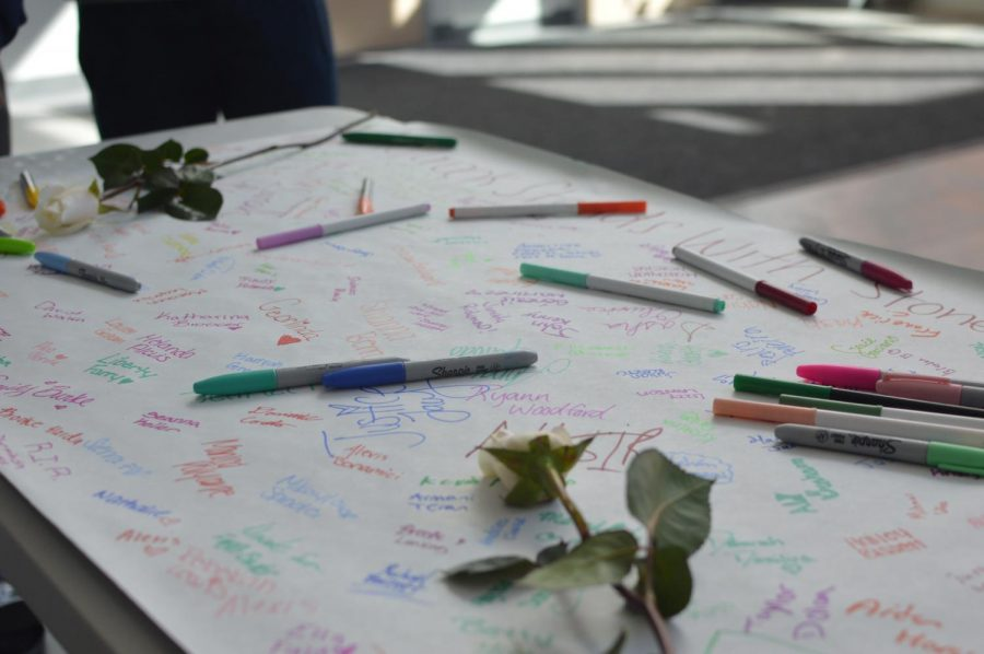 Students+honor+those+who+were+lost+by+signing+their+names+to+a+banner+during+the+walkout+on+March+15th.