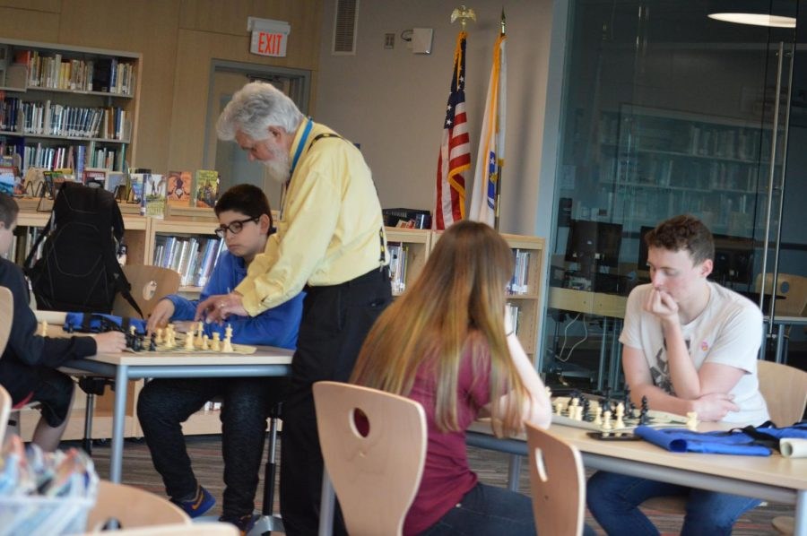 Mr. Tarnopol teaching students how to play chess.