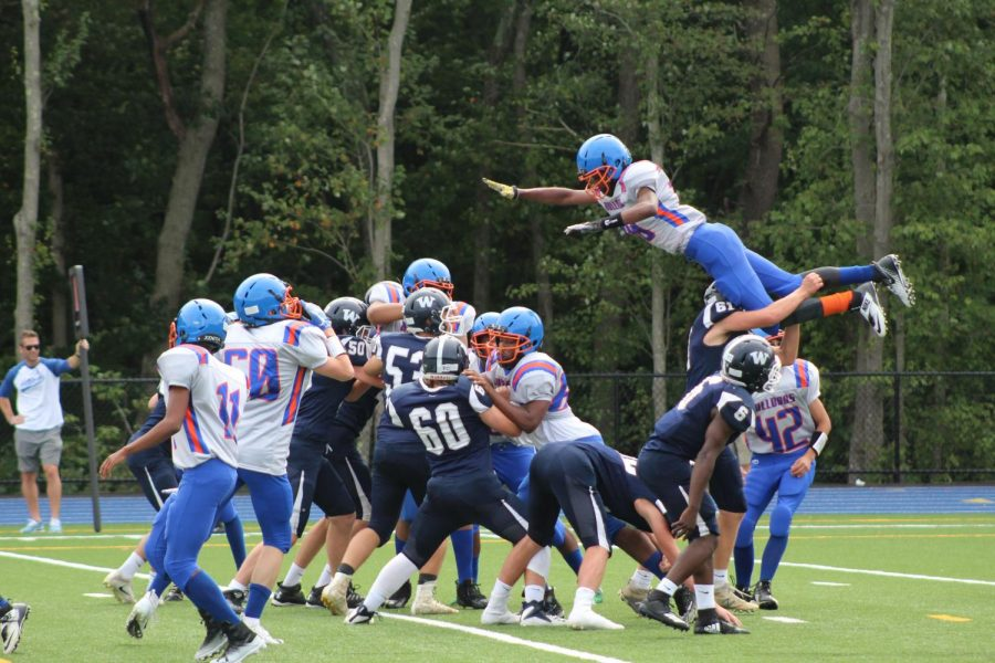 Player Jamiel Clayton-Cape jumping over his opponents to retrieve the ball.