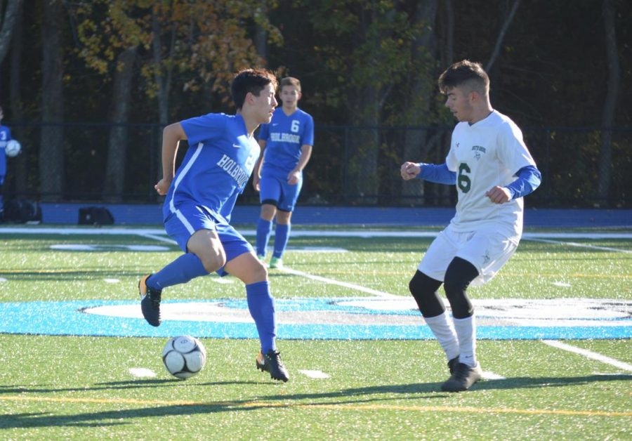 Liam Kelly keeps ball away from opponent.