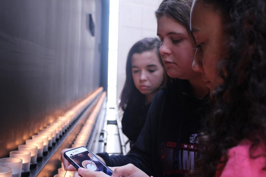 Elizabeth White, Holly Davis, and Tiana Docanto light a candle at the Holocaust Memorial Museum.