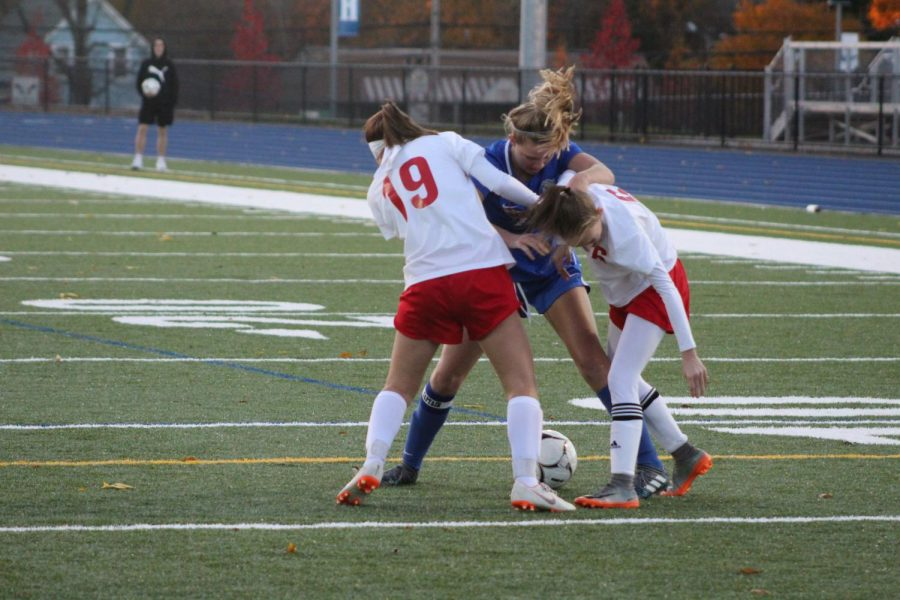 Riley Cochran battles two Bishop Connolly players for the ball