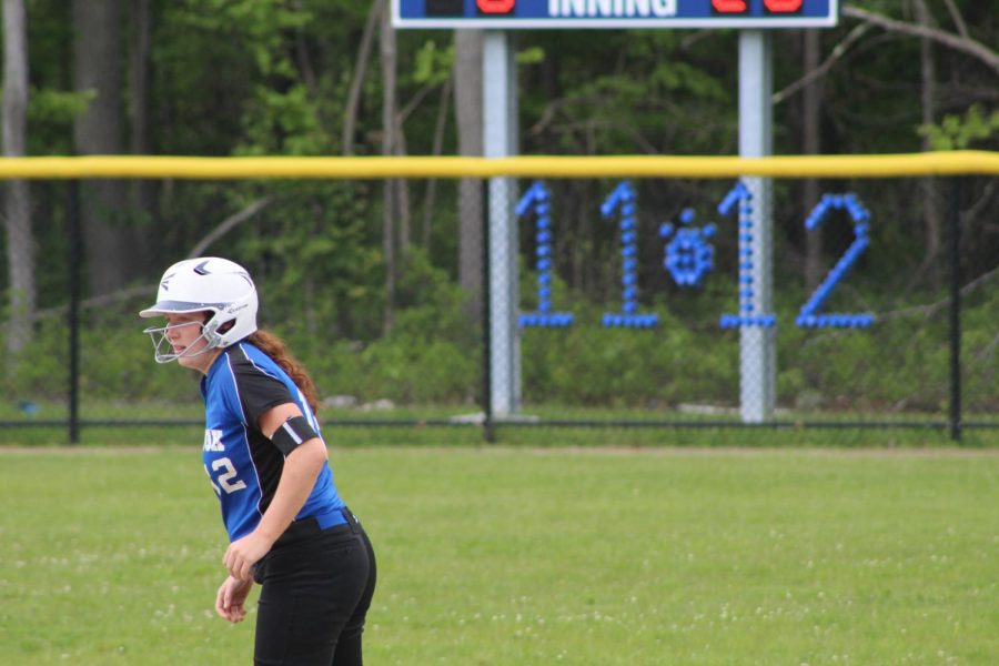 Senior Katelin Andrews at second base with the senior numbers, 11 and 12, displayed on the fence