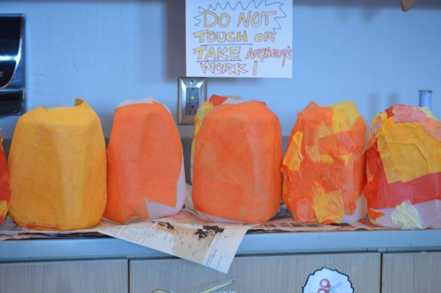 Group of pumpkins being worked on by 6th grade art students