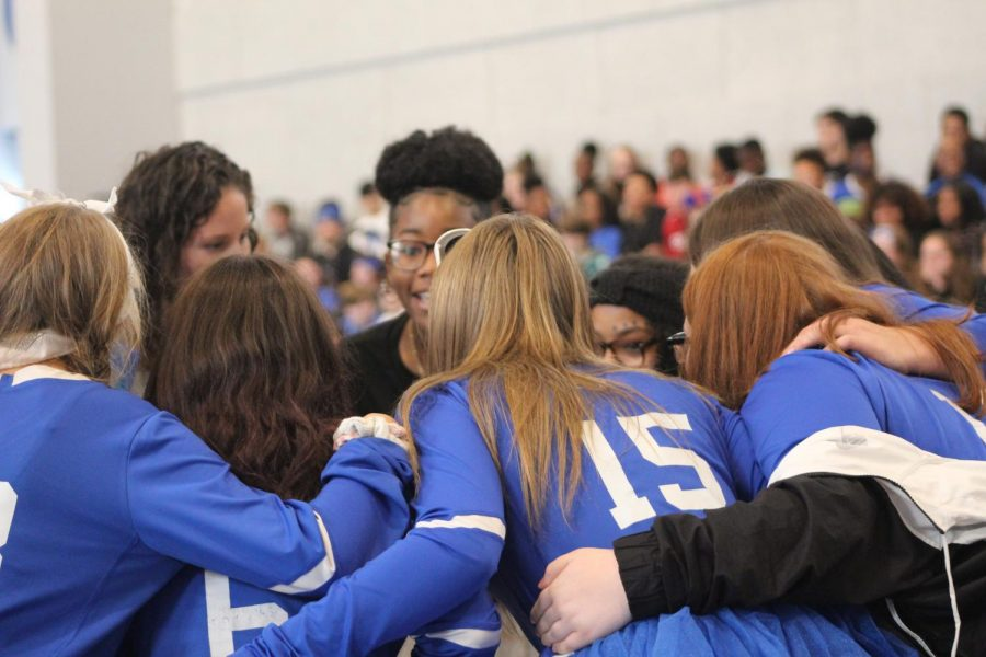 The JV volleyball team celebrates together.
