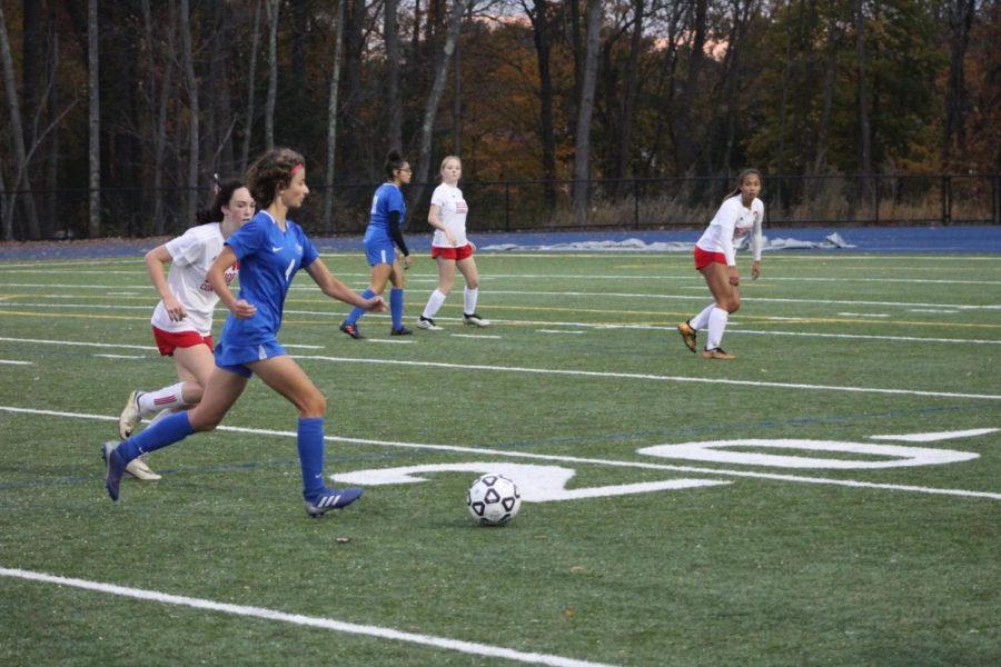 Sara Sullivan dribbles past opponent.