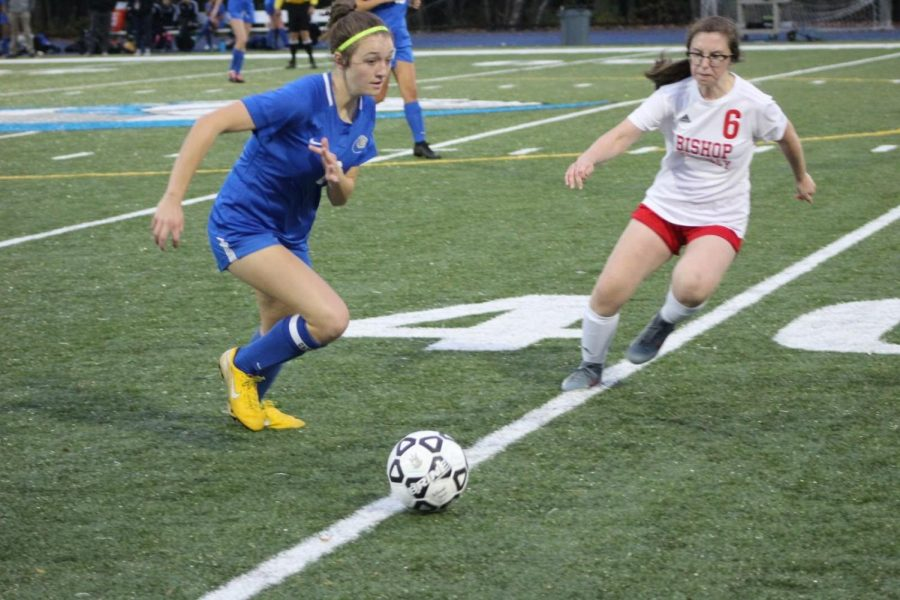 Lucy Ambroult runs toward the ball before opponent.