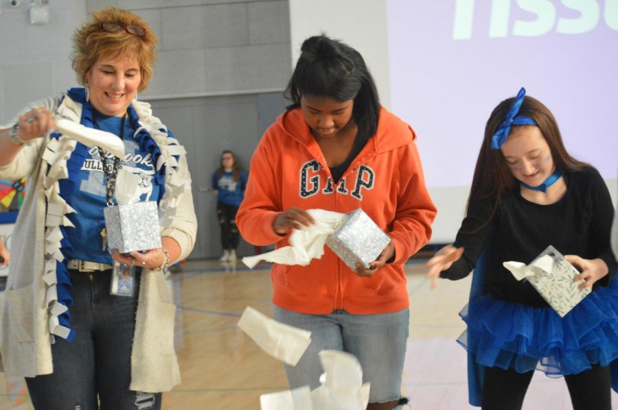Mrs. Clougher, Iyanna Louis, and Kylie Harer race to pull out all the tissues in the box first.
