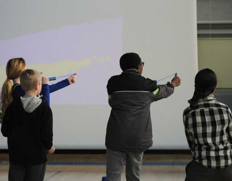 Four 6th graders attempt to hit a moving target with foam string rockets.